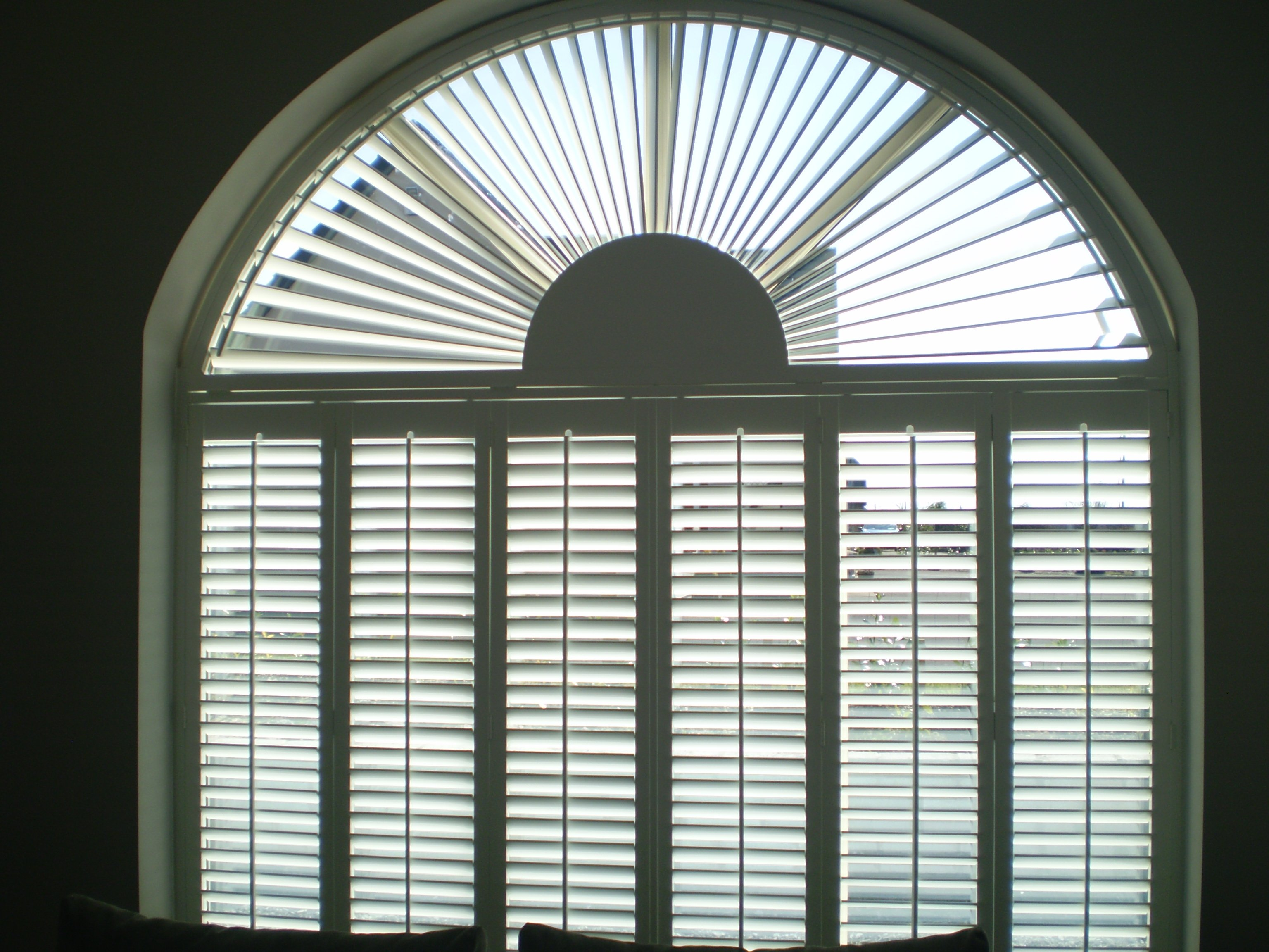 Arched window with sunburst shutter over six panels